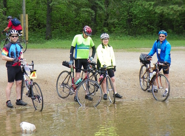 Dipping tires at headwaters of Ol' Man River, at Itasca State Park,  on the 2012 Mississippi River Ride -photo HaveFunBiking