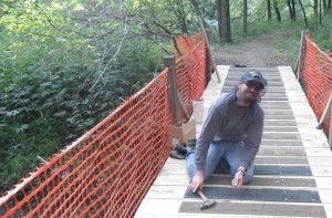 A volunteer putting the finishing touches on a bridge so riders can start breaking in the new trail system in Austin, MN.