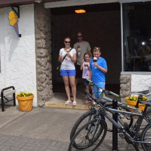 Here a family, coming out of Two Scoops Ice cream Shop, in  Anoka MN, enjoys a a summer treat.