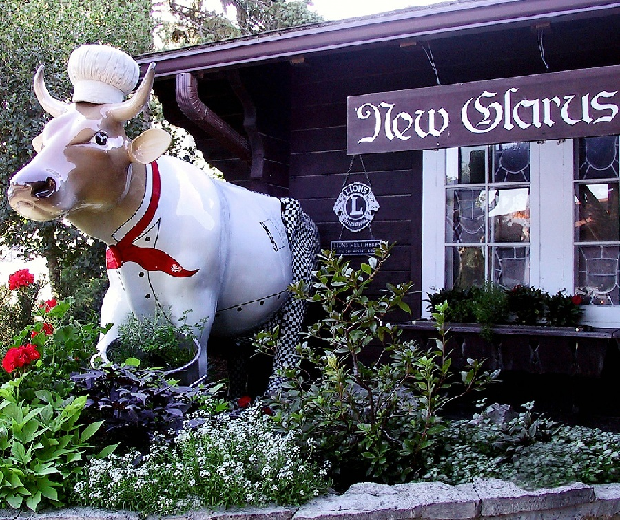 A statute of a cow graces the front of a business in New Glarus, WI.