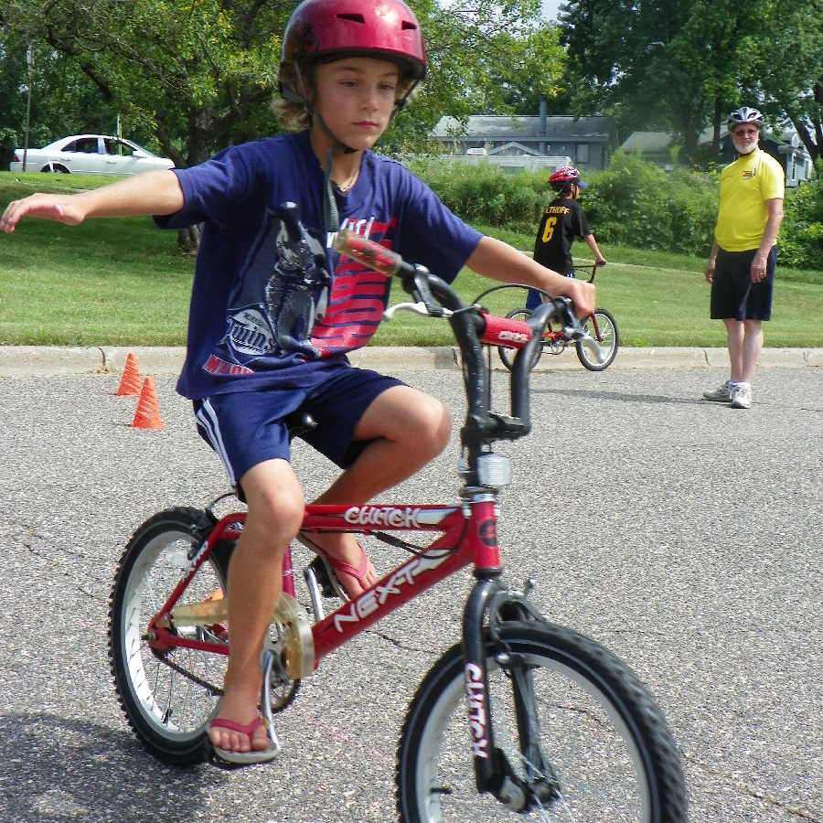 Learning to use turn signals at a Wise Bike Wednesdays rodeo training course lead by instructors of BikeMN, so biking to school is fun.