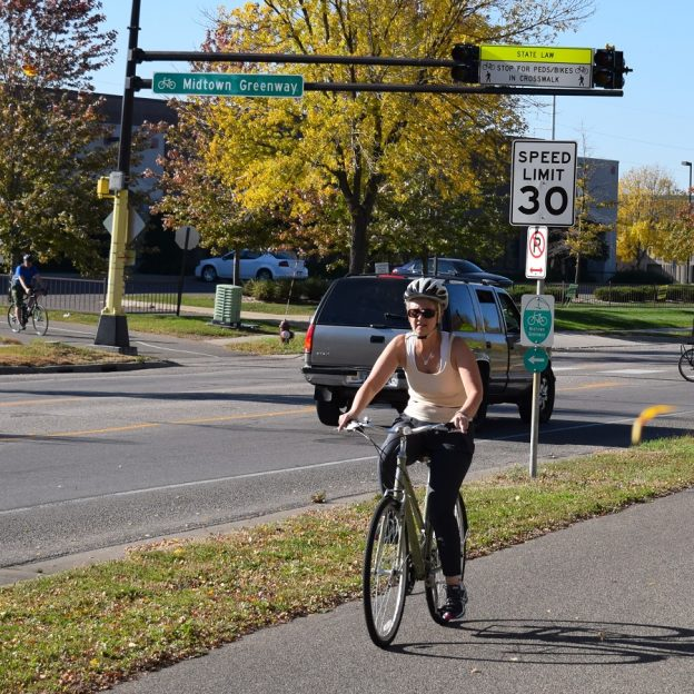 Another beautiful fall day to enjoy a bike ride. Here this cyclist is riding along the Greenway Trail, in Minneapolis, MN.