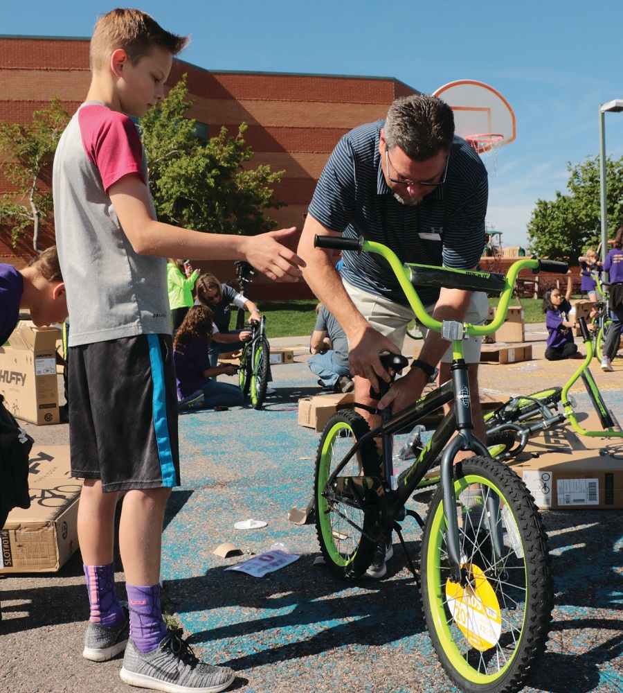 This father, son team assemble a bike for a school program.