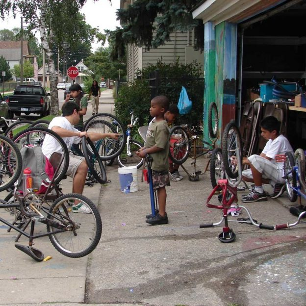Discovering how things work here is a group of neighborhood kids learning about bicycle maintenance.