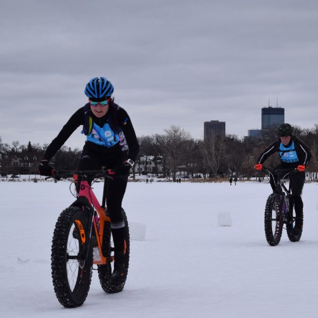 this biker chick is having fun riding into the Monday morning sun in across Lake of the Isles, in Minneapolis Minnesota, Preparing for the Penn Cycle Fat Bike Loppet