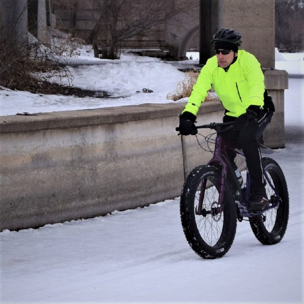 Here in today's bike pic this bold north biker dude commutes to work on his fatty, through the channel from Lake of the Isles to Lake Calhoun, into the Monday morning sun, in Minneapolis.
