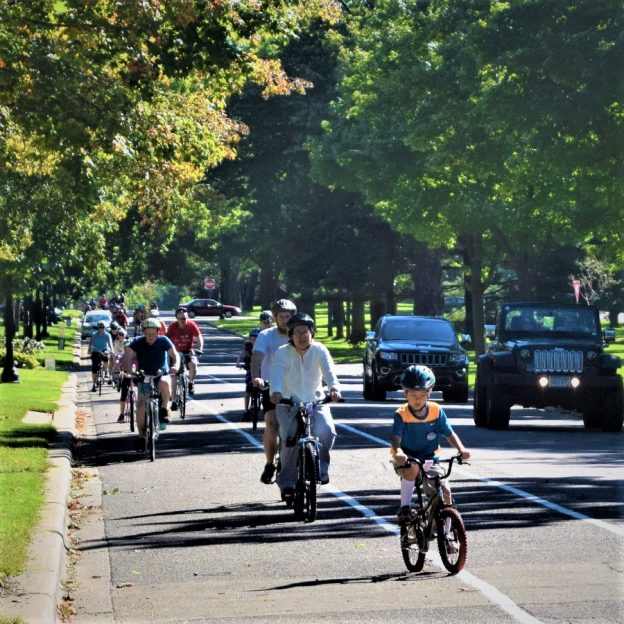 Fond summer memories riding the Saint Paul Classic Bicycle Tour, as this family of cyclists demonstrates riding down Summit Avenue, in St Paul's historic district.