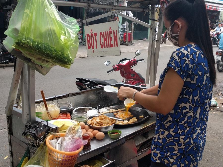 Vietnamese street vendor making savory omelettes