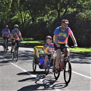 In this bike pic, this family knows where the shaded lanes are in St. Paul, MN to stay cool. Dressed in matching tie-dyed T-shirts this family know that riding along Summit Avenue offers protection from the hot sun.