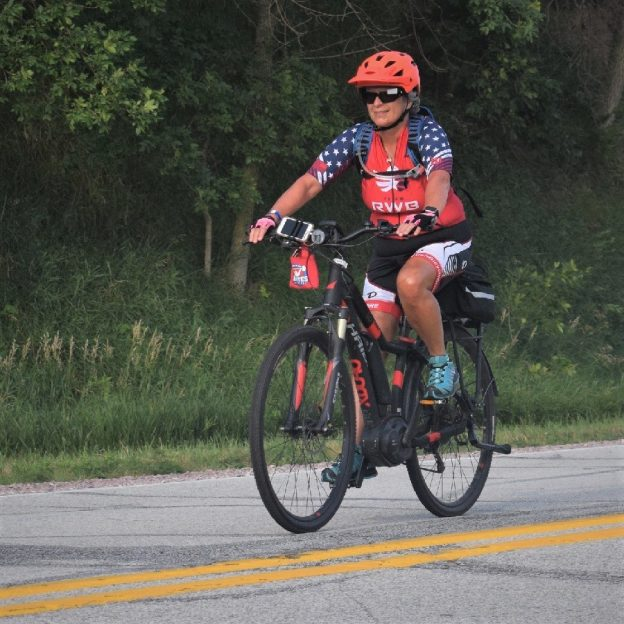 In this bike pic, here is another biker chick pedaling here electric assist bicycle down the road into the Thursday morning sun. This picture was captured last week on RAGBRAI 2018.
