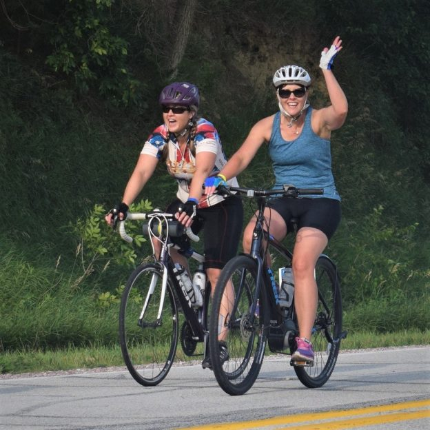 Here in this bike pic we captured a couple biker chicks having fun pedaling into the morning sun. One on an e-bike riding across Iowa on RAGBRAI 2018.