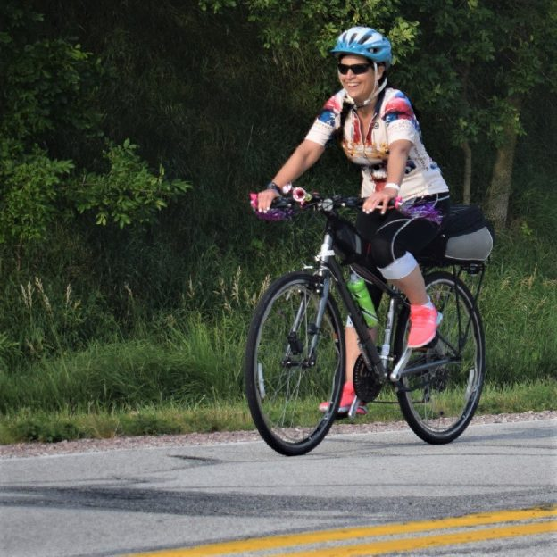 Here in this bike pic we captured another biker chick having fun pedaling into the morning sun, riding across Iowa. See more fun photo on the RAGBRAI 2018 website.