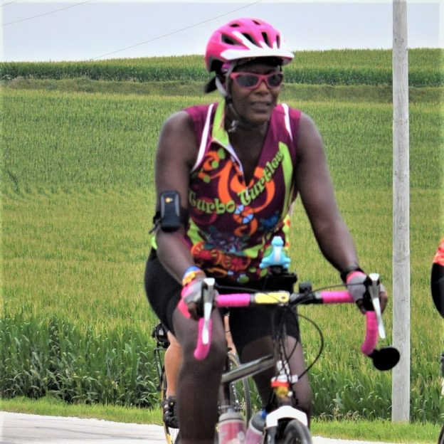 Here in this bike pic, we captured a biker chick having fun pedaling into the Monday morning sun, riding across Iowa. See more fun photo on the RAGBRAI 2018 website.