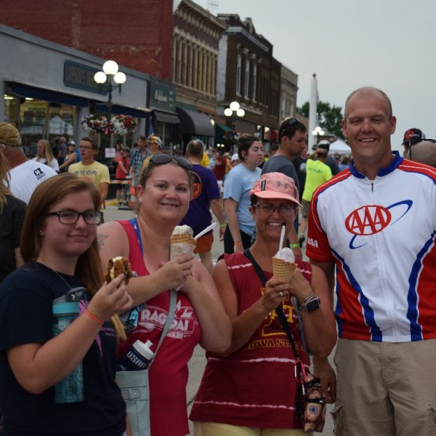 Sharing an ice cream treats with friends after a hard days ride, in front of the AAA - The Auto Club Group's booth, on the Register's Annual Great Bicycle Ride Across Iowa (RAGBRAI). This year's bike tour started in Onawa finished in Davenport for a total of 428 miles.