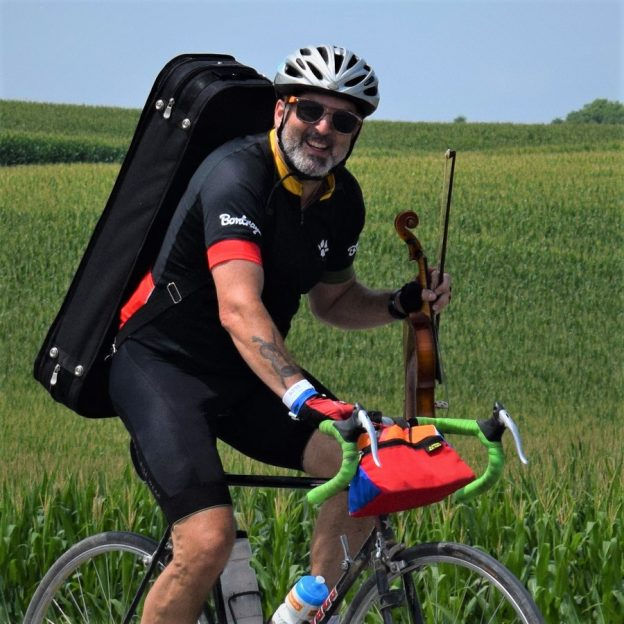 This Bike Pic Friday, digging through the summer archives we found this biker dude with a fiddle in hand enjoying the Iowa countryside, on the ride across Iowa, RAGBRAI.