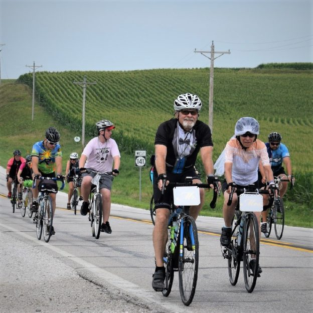 Here in this bike pic, digging through our summer archives, we captured this biker couple wearing altered wedding attire as they pedaled across Iowa. See more fun photos on the RAGBRAI 2018 website.