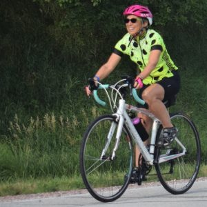 Here in this bike pic, we captured a biker chickhaving fun pedaling into the Monday morning sun, riding across Iowa.