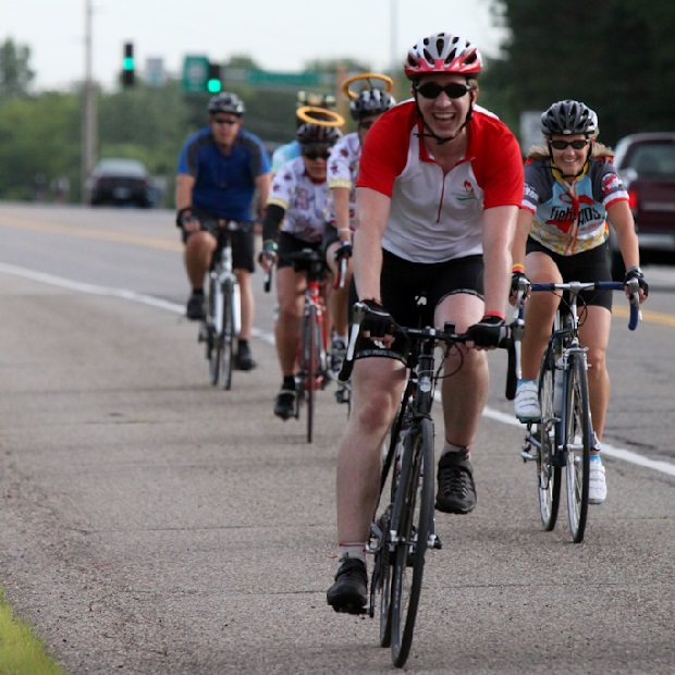 Here a bike rider on a Red Ribbon Bike Ride, in the Twin Cities, is flanked by angels on cycles.