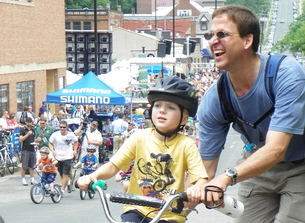 Dad enjoying time with his son at the North Star Bike Festival and Grand Prix in Stillwater, MN