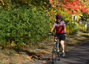 Here a young lady rides her bike along a trail in the Twin Cities Gateway area as the fall colors peak.