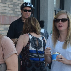 Here in this photo a lady stops for an ice cream treat  while riding her bike with a group of friends. in San Diego, CA.