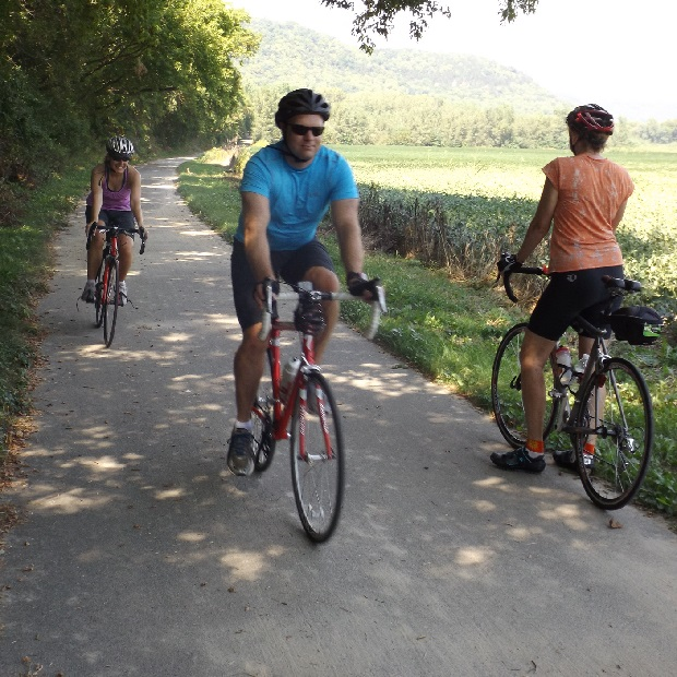 "Bike riders enjoying the Root River Trail with the majestic bluffs in view and whispering in the breeze, ""Come Explore."""